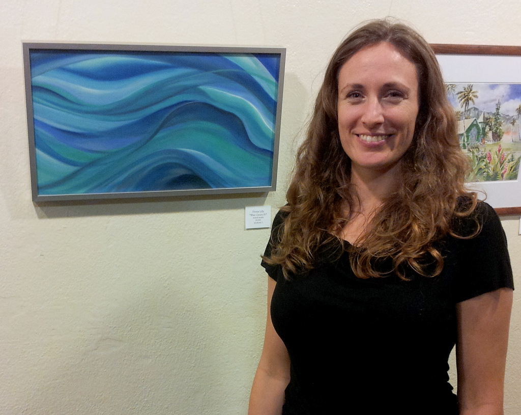 Donia Lilly with her aquamarine pastel, mixed media painting at Women Artists of Kauai Museum opening
