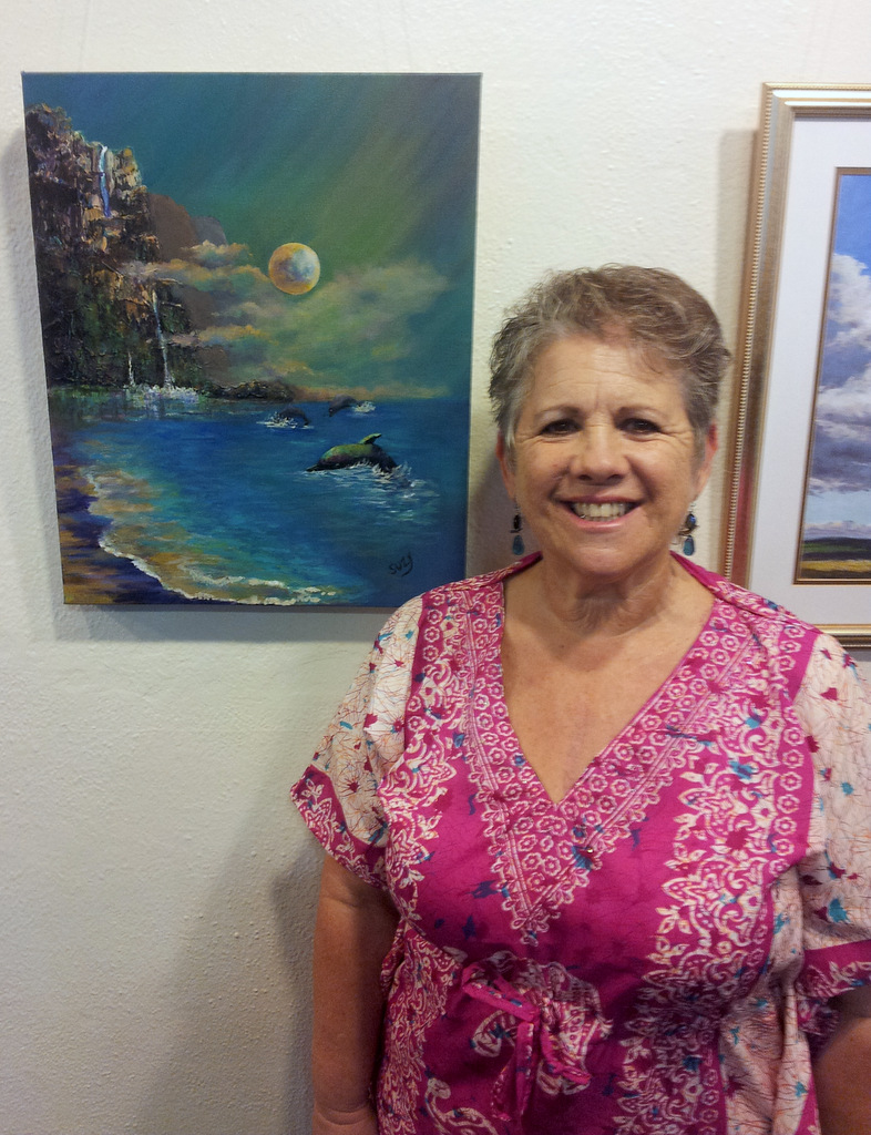 Suzy Staulz with her ocean landscape painting at Women Artists of Kauai Museum opening